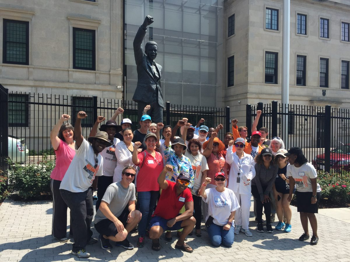Volunteers gather in front of the South African Embassy's statue of Nelson Mandela